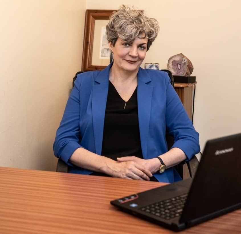 Mairead Heagney sitting at a desk with a laptop